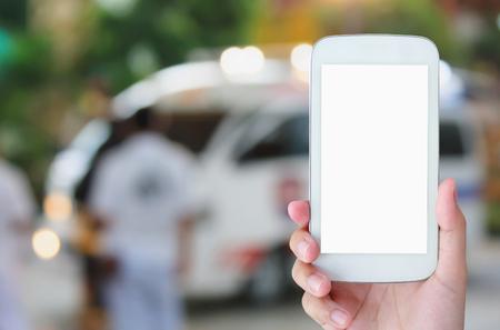 hand houden smartphone met Ambulance reageren op noodoproep achtergrond Stockfoto