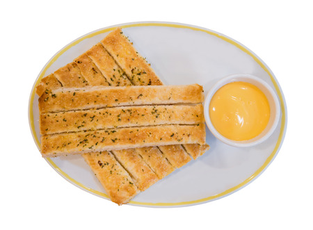 gressins: Fresh breadsticks served with dip sauce on white plate isolated on white Banque d'images