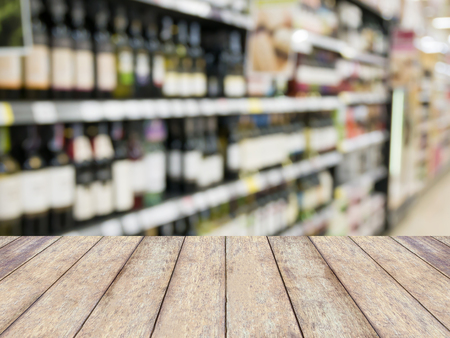 store shelf: wood table over blur wine bottles on shelf in wine store, product display Stock Photo