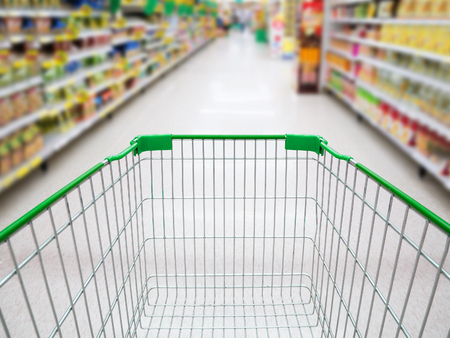 Supermarket interior, supermarket aisle with empty green shopping cart background, shopping in supermarket concept