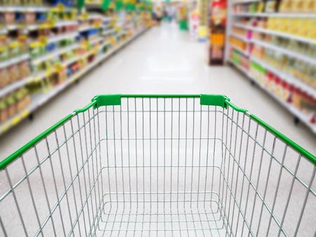 Supermarkt interieur, supermarktdoorgang met lege groen boodschappenwagentje achtergrond, winkelen in de supermarkt begrip Stockfoto