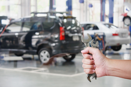 auto repair: Hand of professional Auto mechanic with wrench, Auto repair service Stock Photo