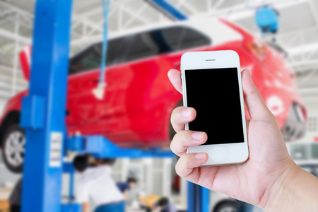 servicing: woman hand hold touch screen mobile smart phone with car garage servicing centre blur background