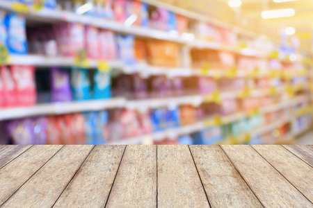 wood table top over detergent shelves in supermarket or grocery store blurred background, for product display