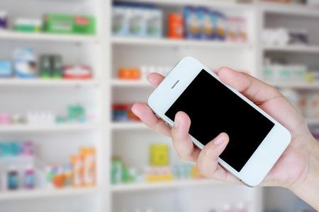 pharmacist hand holding smart phone with blur some shelves of drug in the pharmacy drugstore
