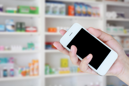 pharmacist hand holding smart phone with blur some shelves of drug in the pharmacy drugstore Banco de Imagens - 63440003