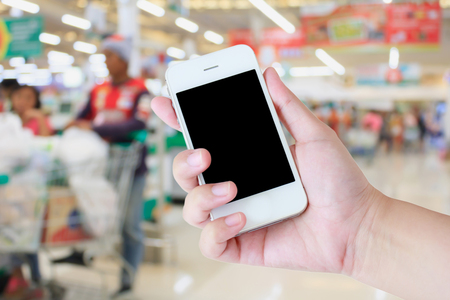 supermarket checkout: Hand holding mobile phone at supermarket checkout background, digital wallet concept