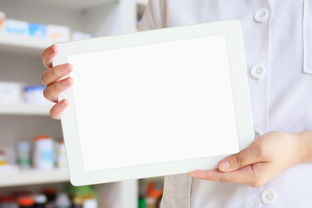 Weiblicher Apotheker, der Tablet-Computer über Apothekendrugstorehintergrund zeigt Standard-Bild - 63433697