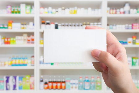 medicine box: Close up pharmacist hand hold medicine box package with shelves of drugs in the pharmacy