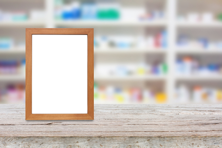 over the counter: wood photo frame on the pharmacy counter over blur shelves of drug in the pharmacy drugstore background