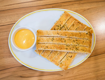 Fresh breadsticks served with dip sauce on white plate