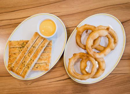 gressins: rondelles d'oignon frit et gressins sur la plaque blanche