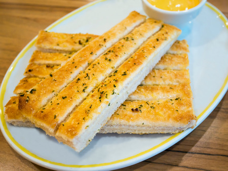 breadstick: Fresh breadsticks served with dip sauce on white plate