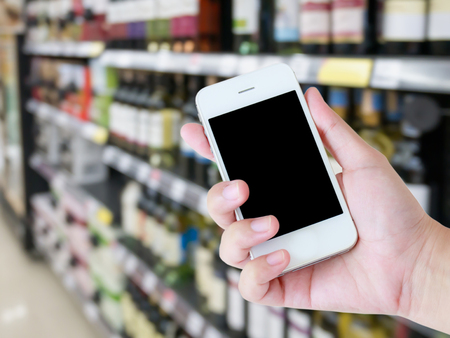 store shelf: hand hold mobile smartphone with blur wine bottles on shelf in wine store