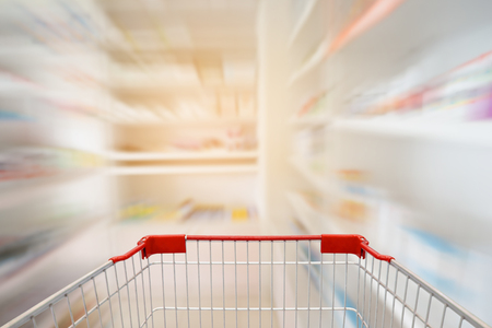shopping cart in the pharmacy store shelves interior with motion blurred background