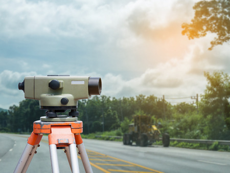 tacheometer: Surveyor equipment tacheometer or theodolite with road construction site background