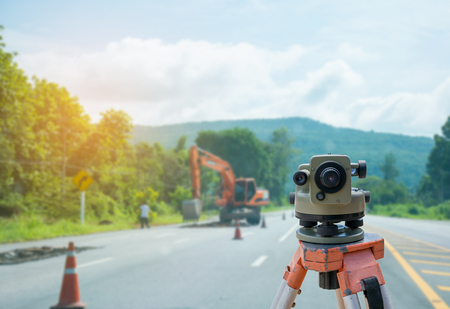 theodolite: Surveyor equipment tacheometer or theodolite with road construction site background