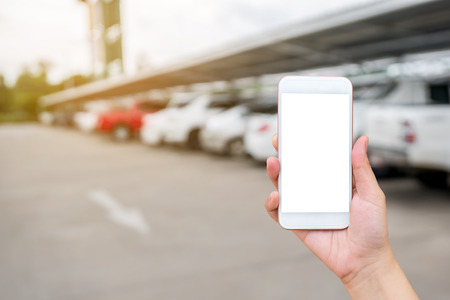 Woman hand showing smart phone with blank white screens display on blurred car in parking lot