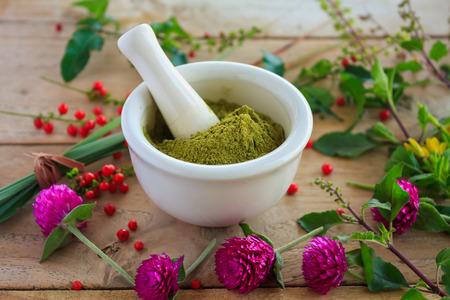 green herbs: Fresh herbs powder in the mortar on wood background, alternative medicine