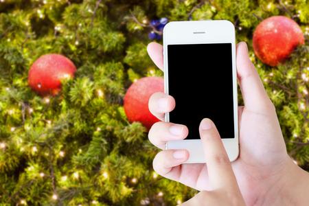 christmas party concept hand holding mobile smart phone with christmas lights bokeh on xmas tree