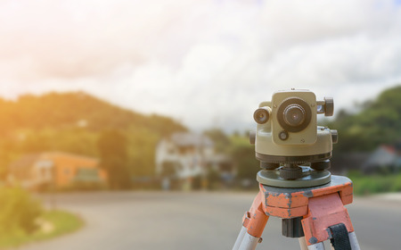 theodolite instrument for road construction surveyor equipment with road construction site works blur background Stock Photo