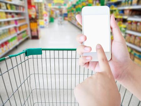 Vrouwelijke hand die mobiele slimme telefoon op Supermarktdoorgang met de achtergrond van het boodschappenwagononjabloon houden, die in supermarktconcept winkelen