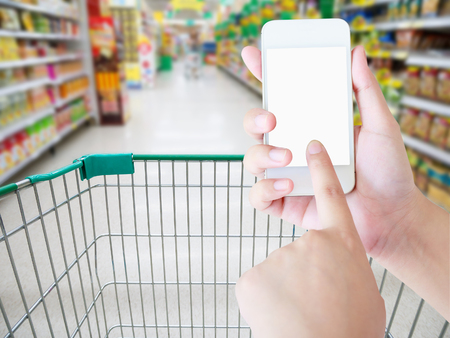 Female hand holding mobile smart phone on Supermarket aisle with shopping cart blur background, shopping in supermarket concept