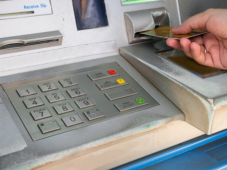 technology transaction: female hand inserting ATM card into ATM bank machine to withdraw money
