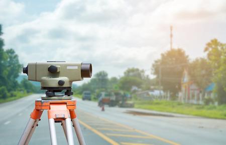 teodolito: El topógrafo equipo de taquímetro o teodolito con el fondo del sitio de construcción de carreteras Foto de archivo