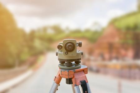 theodolite: road construction site, theodolite instrument for road construction surveyor equipment with road construction site works blur background
