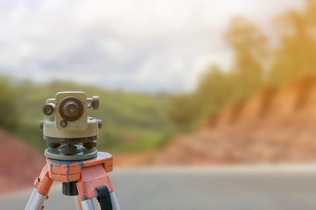 teodolito: sitio de la construcción de carreteras, instrumento teodolito para la construcción de carreteras del equipo del topógrafo con el sitio de construcción de carreteras fondo borroso