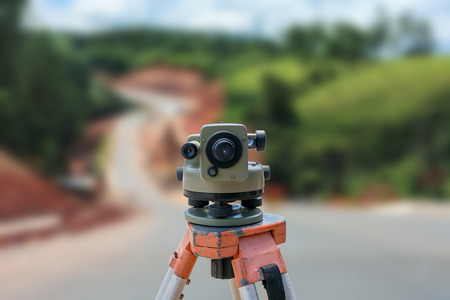road construction site, theodolite instrument for road construction surveyor equipment with road construction site works blur background