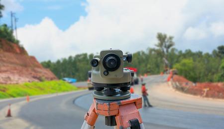 teodolito: teodolito instrumento para la construcción de carreteras del equipo del topógrafo con el sitio de construcción de carreteras fondo borroso