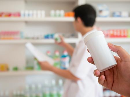 blur image of pharmacist taking medicine from shelf in the pharmacy Banco de Imagens