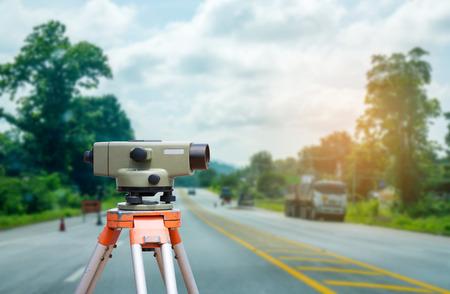 topografo: El topógrafo equipo de taquímetro o teodolito con el fondo del sitio de construcción de carreteras Foto de archivo