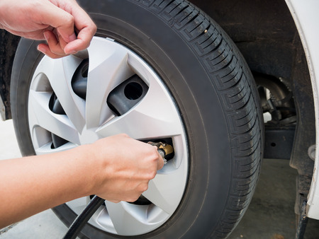 air pressure: man filling air pressure in the car tyre close up