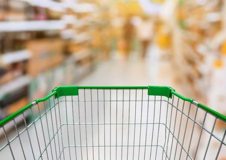 Winkelwagentje met supermarktdoorgang met het product op de planken in onscherpe voor achtergrond