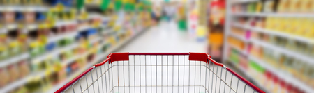 Supermarket interior, supermarket aisle with empty red shopping cart background, shopping in supermarket concept