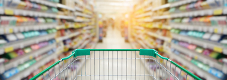shopping cart with supermarket in blurry for background, panorama view