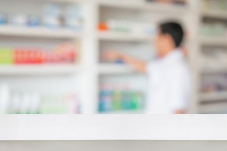Lege witte apotheek tafel teller met vervagen schappen van de drug in de apotheekdrogisterij achtergrond, te creëren voor montage medische product-display Stockfoto