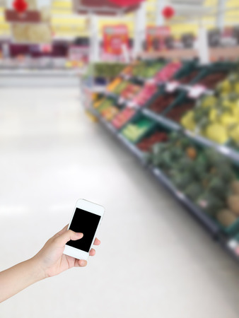 Hand holding mobile phone with Vegetables and fruit on shelf in supermarket blurred background