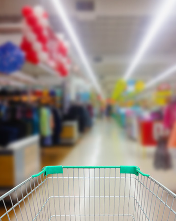 shopping cart with supermarket in blurry for background