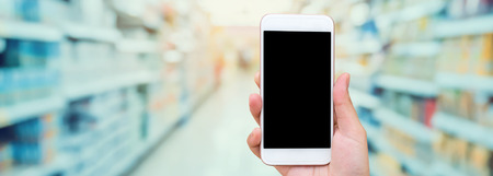 Female hand holding mobile phone with supermarket blur background, online shopping concept Banco de Imagens - 65109721