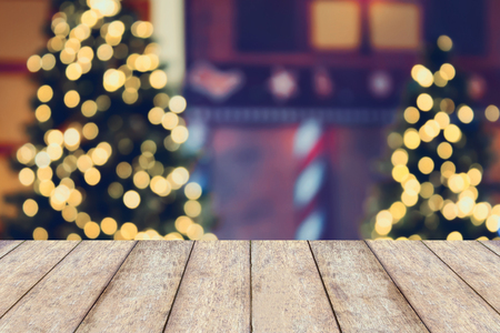 holiday display: Christmas holiday background with empty wooden table top over festive bokeh light decorate on Christmas tree. For create montage product display