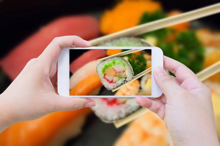 Het nemen van foto van Sushi-maki in eetstokjes met sushi Stockfoto