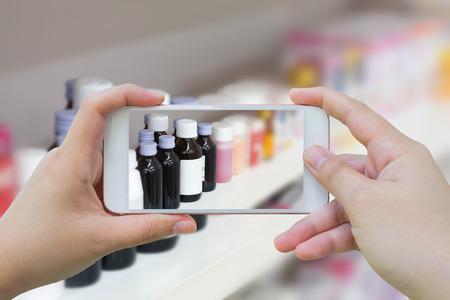 Vrouwelijke hand houden mobiele slimme telefoon fotograferen van medicijnflessen op de apotheek winkelplanken Stockfoto