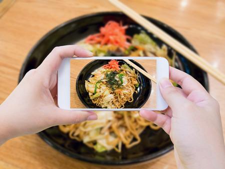 Female using mobile smart phone Taking photo of Yakisoba, japanese fried noodle