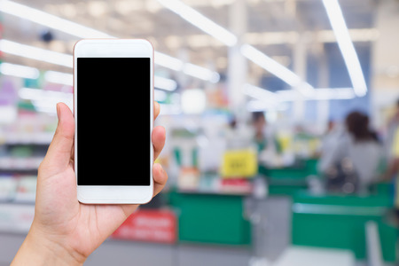 Woman hand holding mobile phone at supermarket checkout background, digital wallet concept