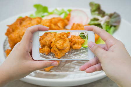 taking photo of fried chicken Japanese style with smartphone Stock Photo
