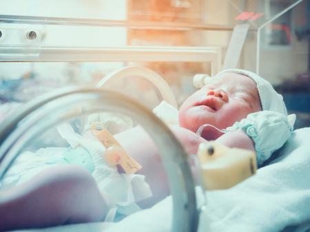 Nieuwgeboren baby zuigeling slapen in de incubator in het ziekenhuis